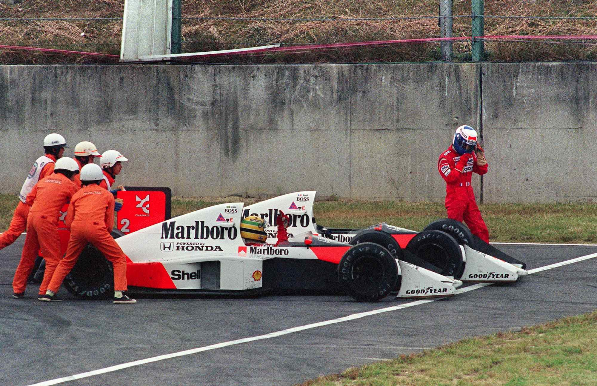 Ayrton Senna of Brazil is given a push from circuit marshals for a restart